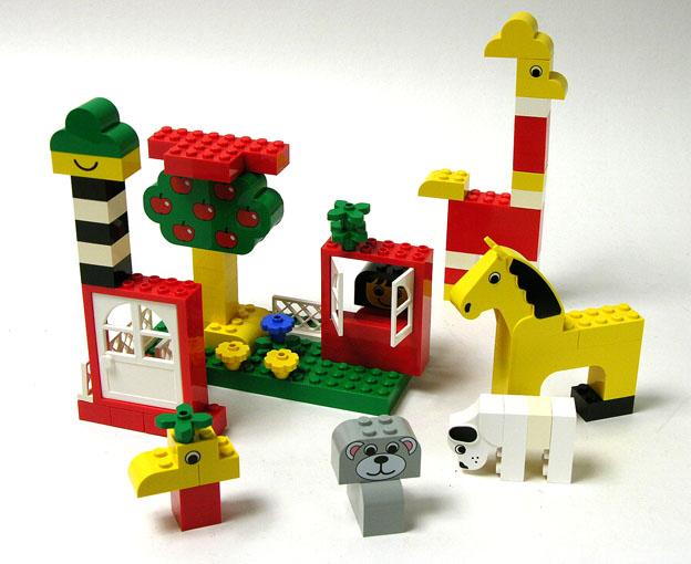 Legoilla leikkivät lapset ja aikuiset